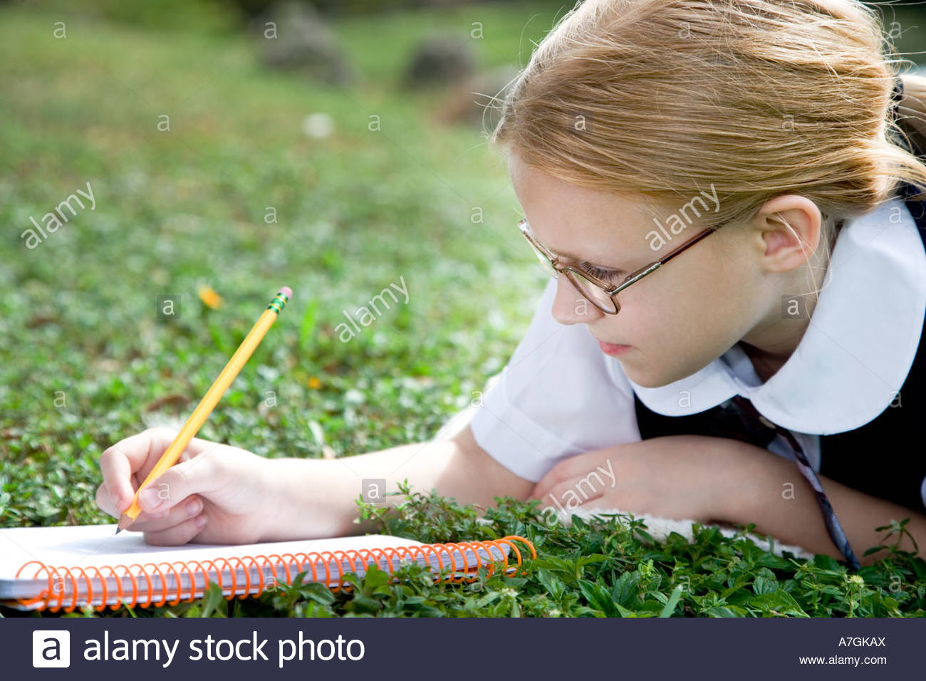 A girl writing in a notebook - Stock Image
