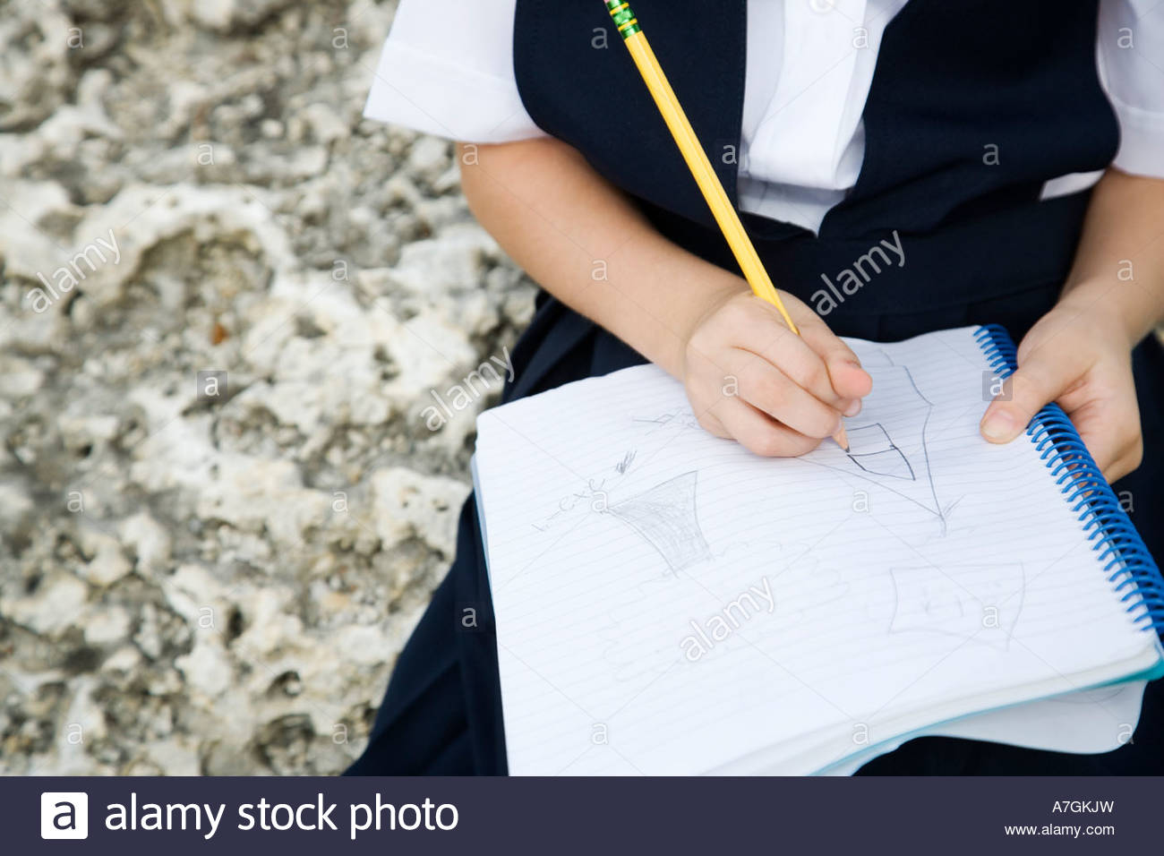 A schoolgirl writing in a notebook - Stock Image