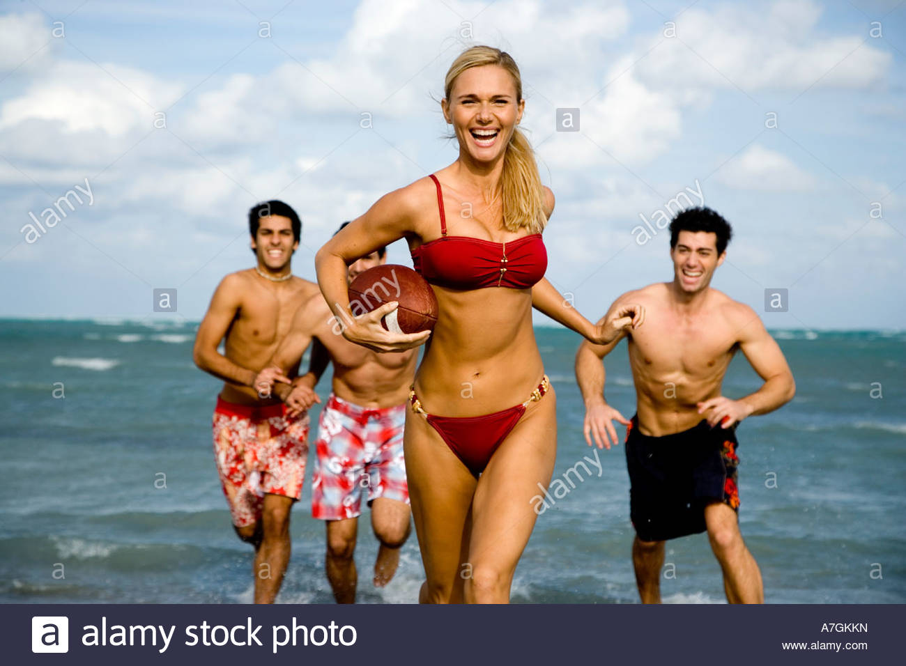 A young woman in a bikini being chased by three men - Stock Image