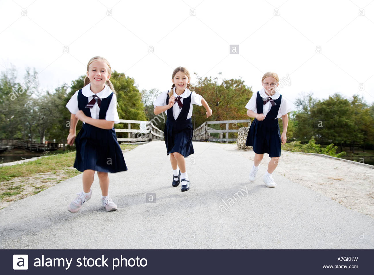 Three schoolgirls running down a road - Stock Image