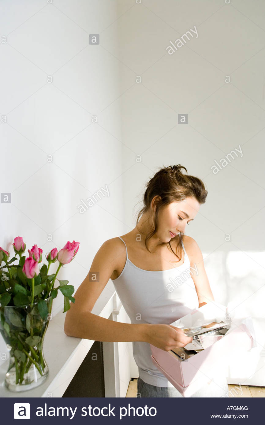 A young woman looking at old photographs - Stock Image