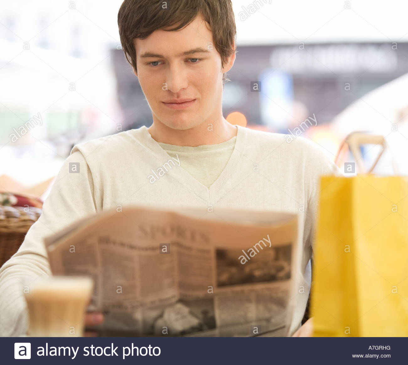 A young man having a break whilst out shopping - Stock Image