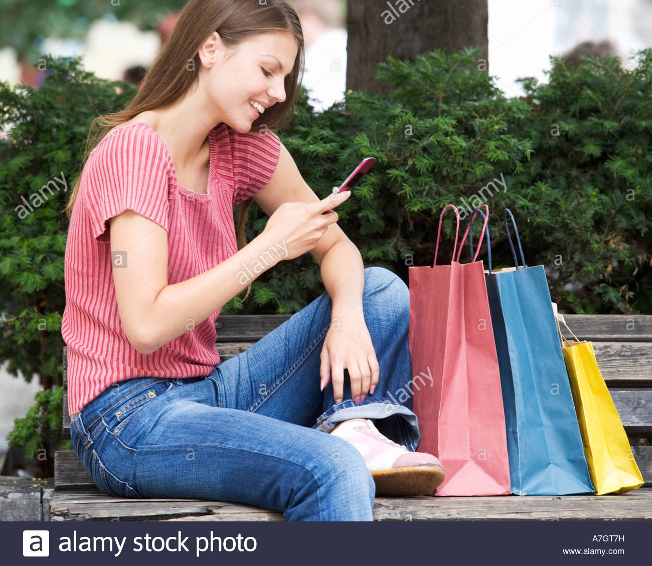 A young woman having a break from shopping - Stock Image