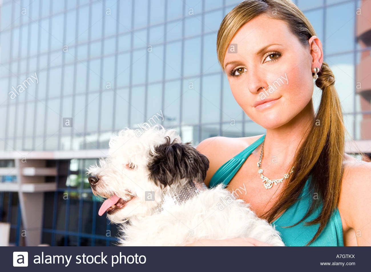 A woman holding a small dog - Stock Image