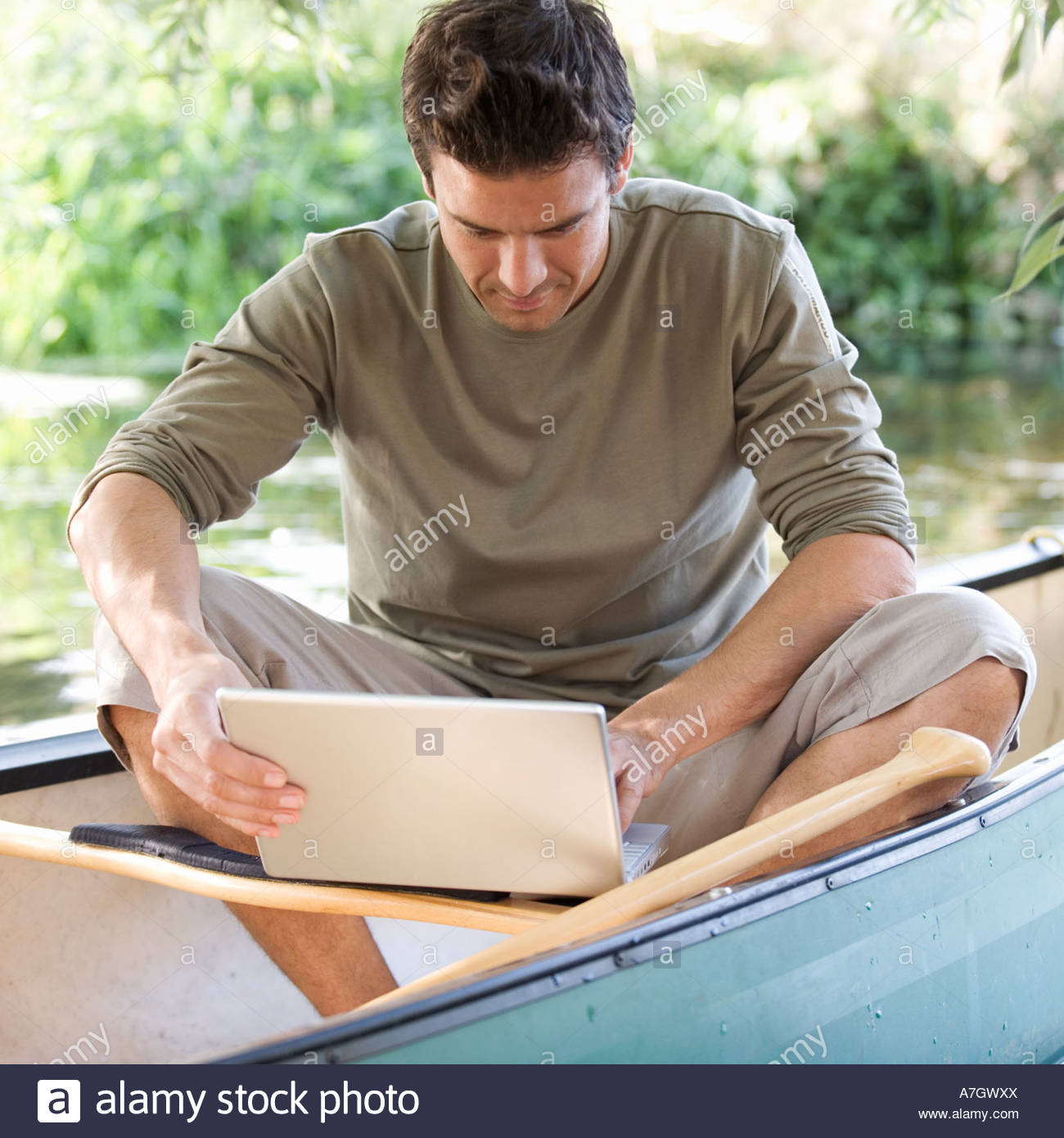 Young man sitting in a boat working on a laptop - Stock Image