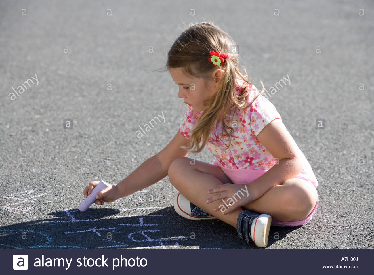 Young girl writing in chalk on the playground - Stock Image