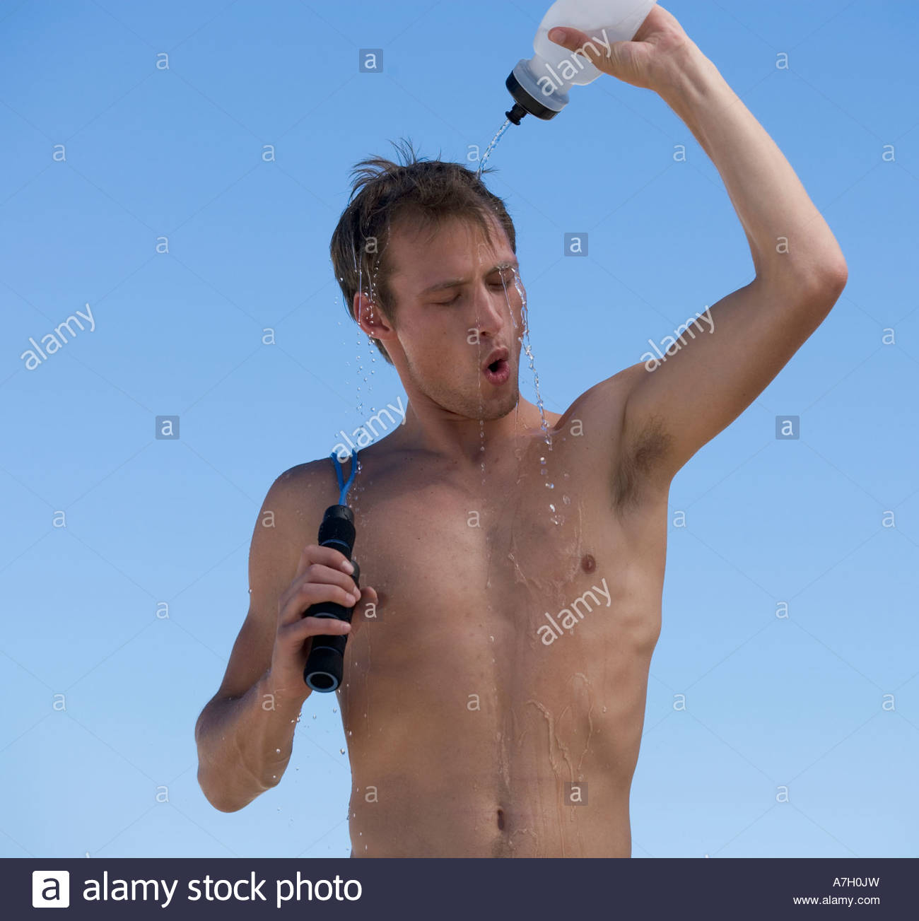 A young man cooling off after exercising - Stock Image