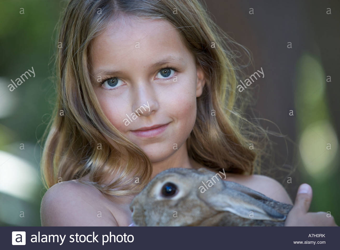 A young girl holding a pet rabbit, close-up - Stock Image