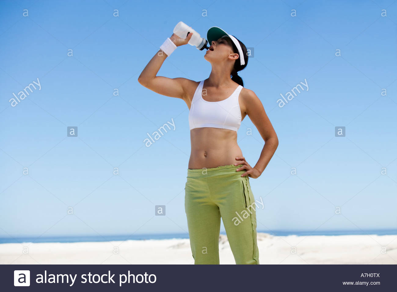 A young woman drinking from a water bottle after exercising - Stock Image