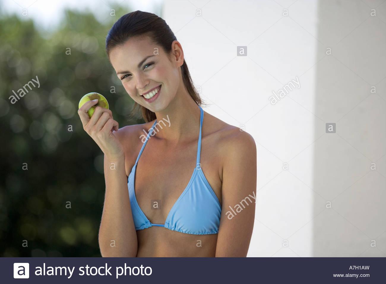 A woman in a bikini eating an apple - Stock Image