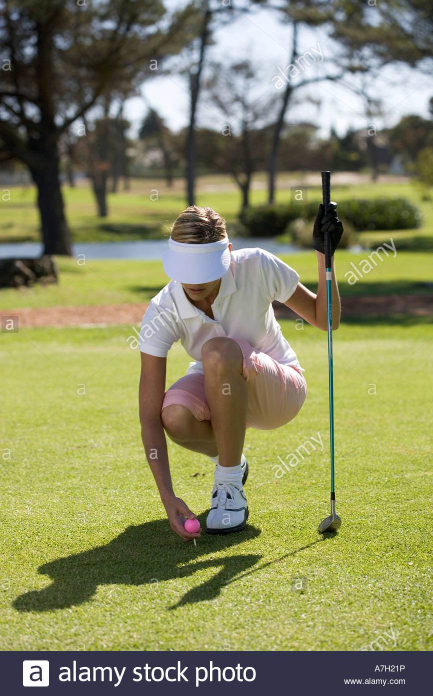 Woman playing golf, teeing up - Stock Image