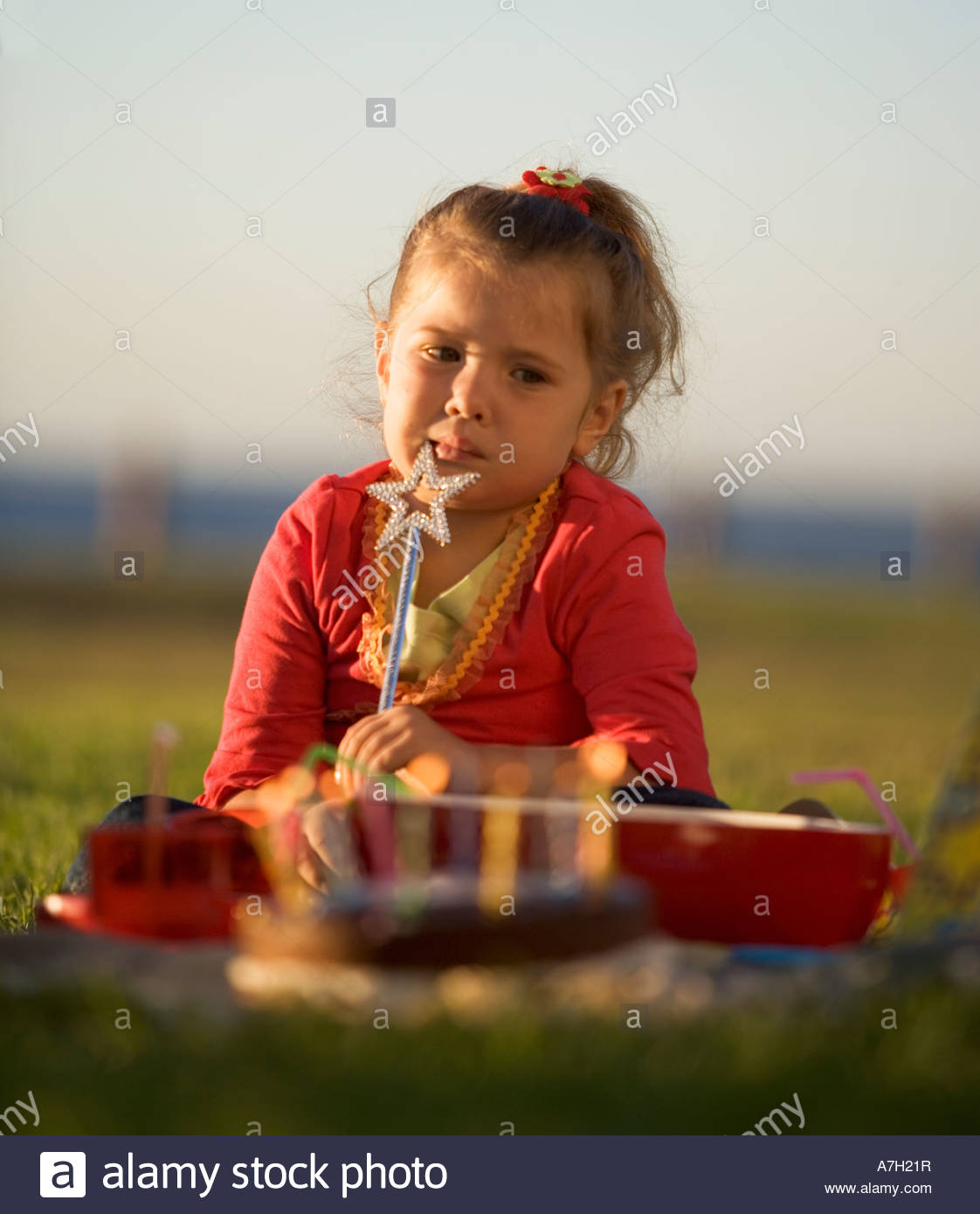 A young girl having a birthday picnic - Stock Image