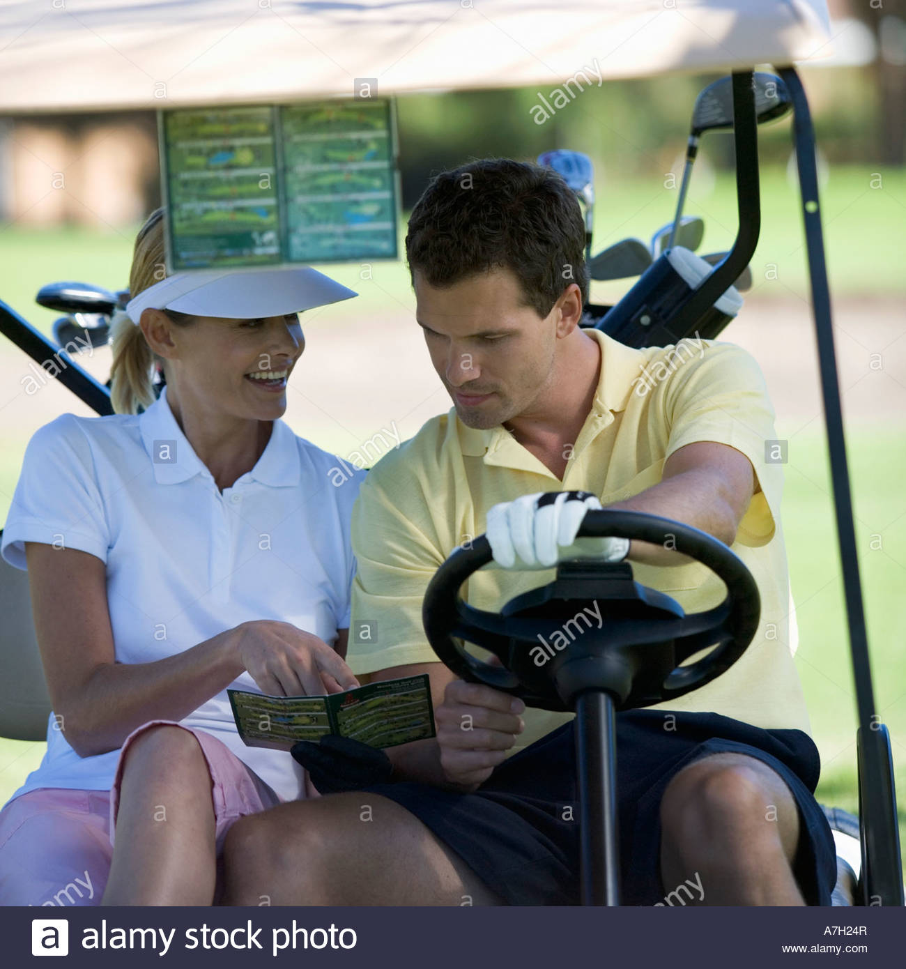Couple in a golf buggy looking at a plan of the course and score card - Stock Image