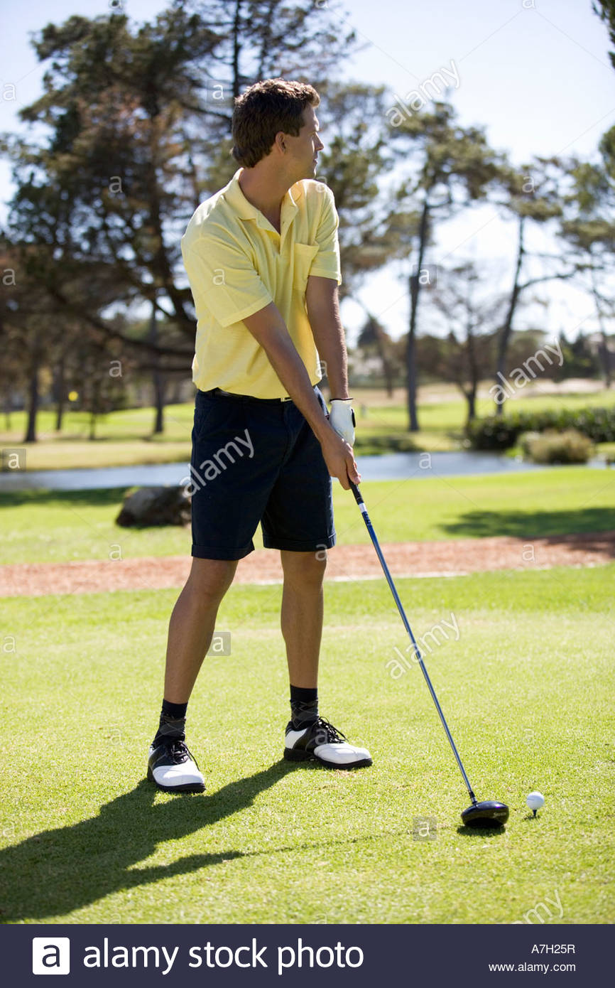 Man playing golf, teeing off - Stock Image