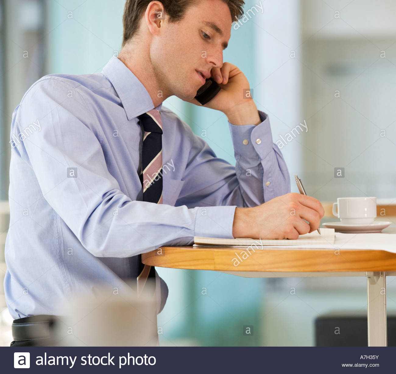 A businessman making a diary appointment - Stock Image