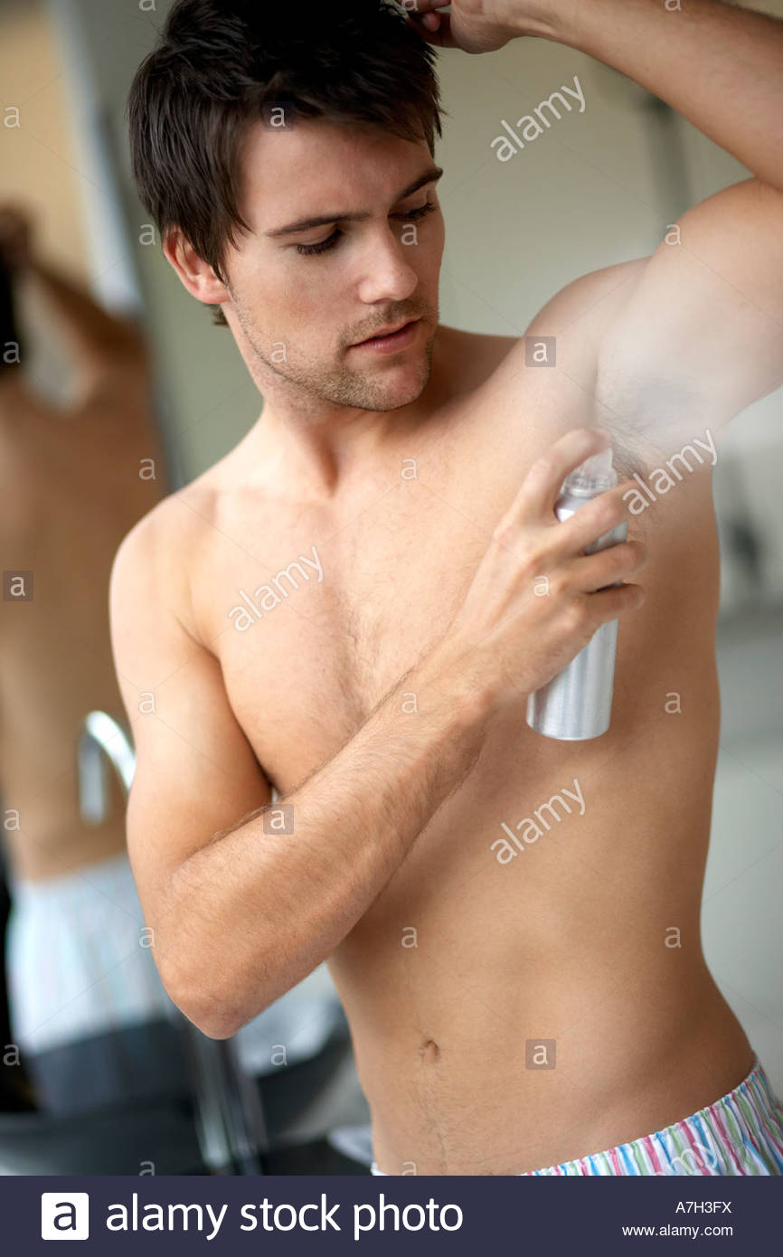 Young man applying deodorant/anti-perspirant - Stock Image