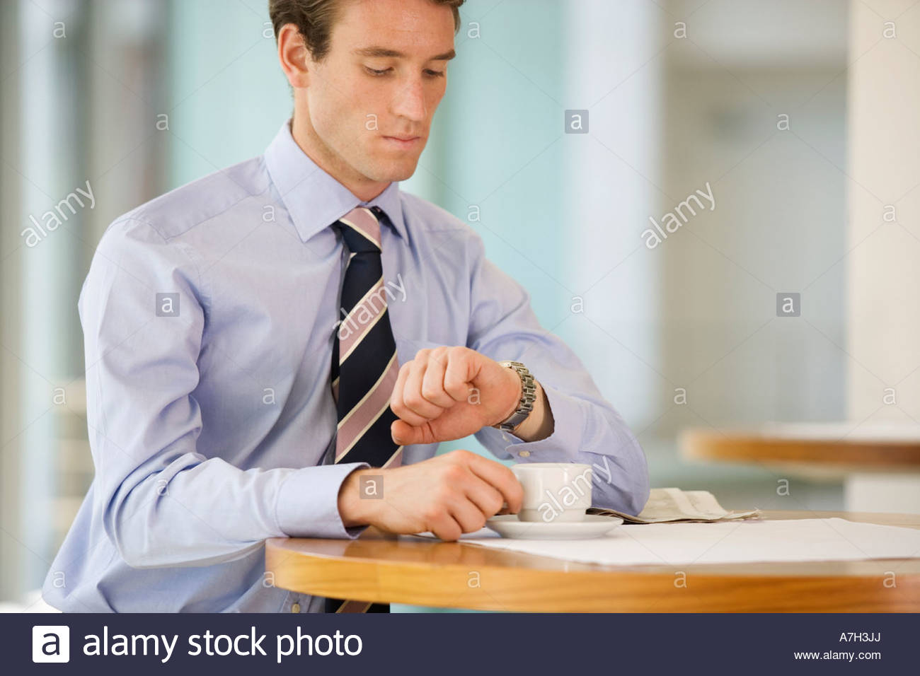 A businessman checking the time on his watch - Stock Image