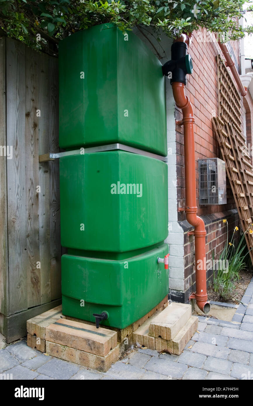 Large green plastic water storage tank collecting and storing rainwater from roof Cheltenham UK & Large green plastic water storage tank collecting and storing Stock ...
