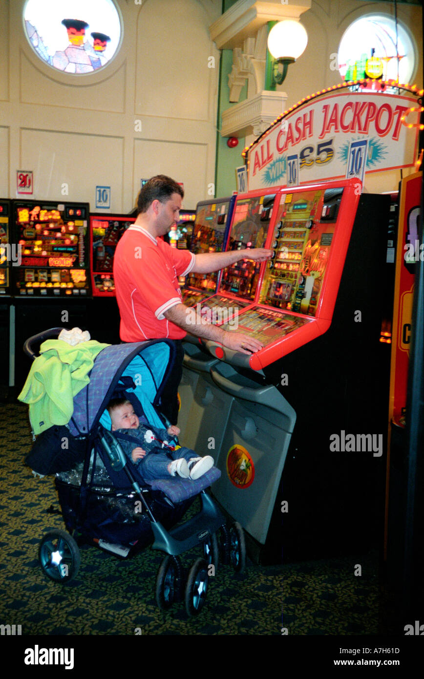 Man and baby in games arcade playing on fruit machines. Stock Photo