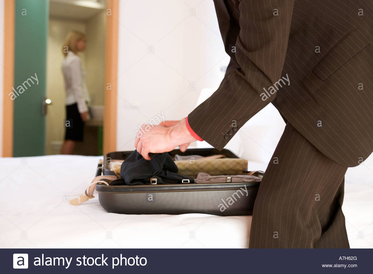 A businessman packing a suitcase - Stock Image