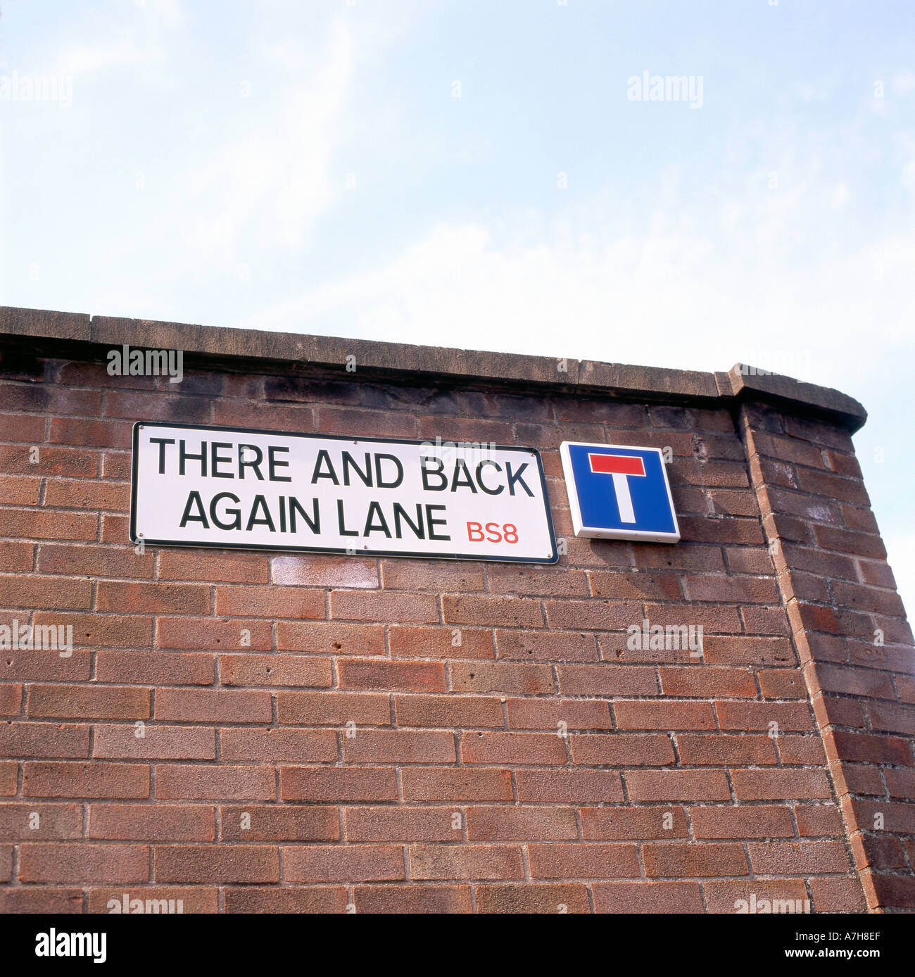 A dead end street sign entitled 'There and Back Again Lane' displayed on a brick wall in Bristol England - Stock Image