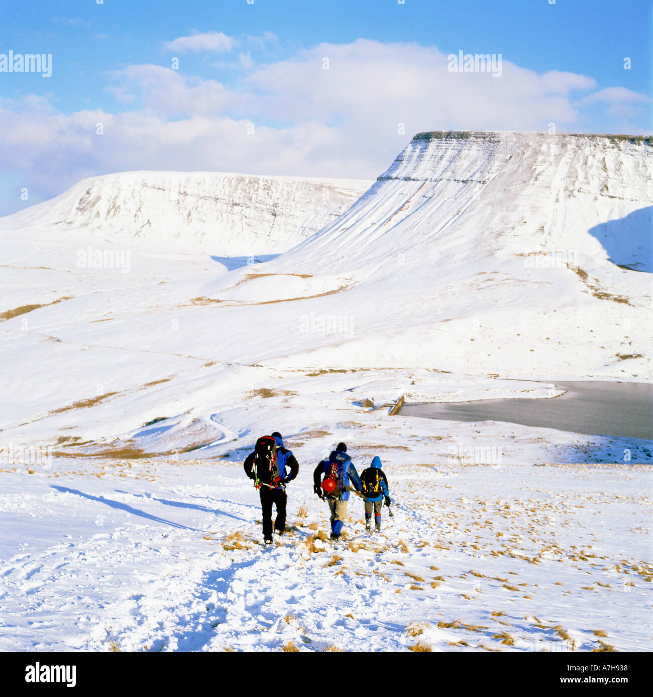 Hikers walking in winter snow to The Black Mountain Llandeusant in