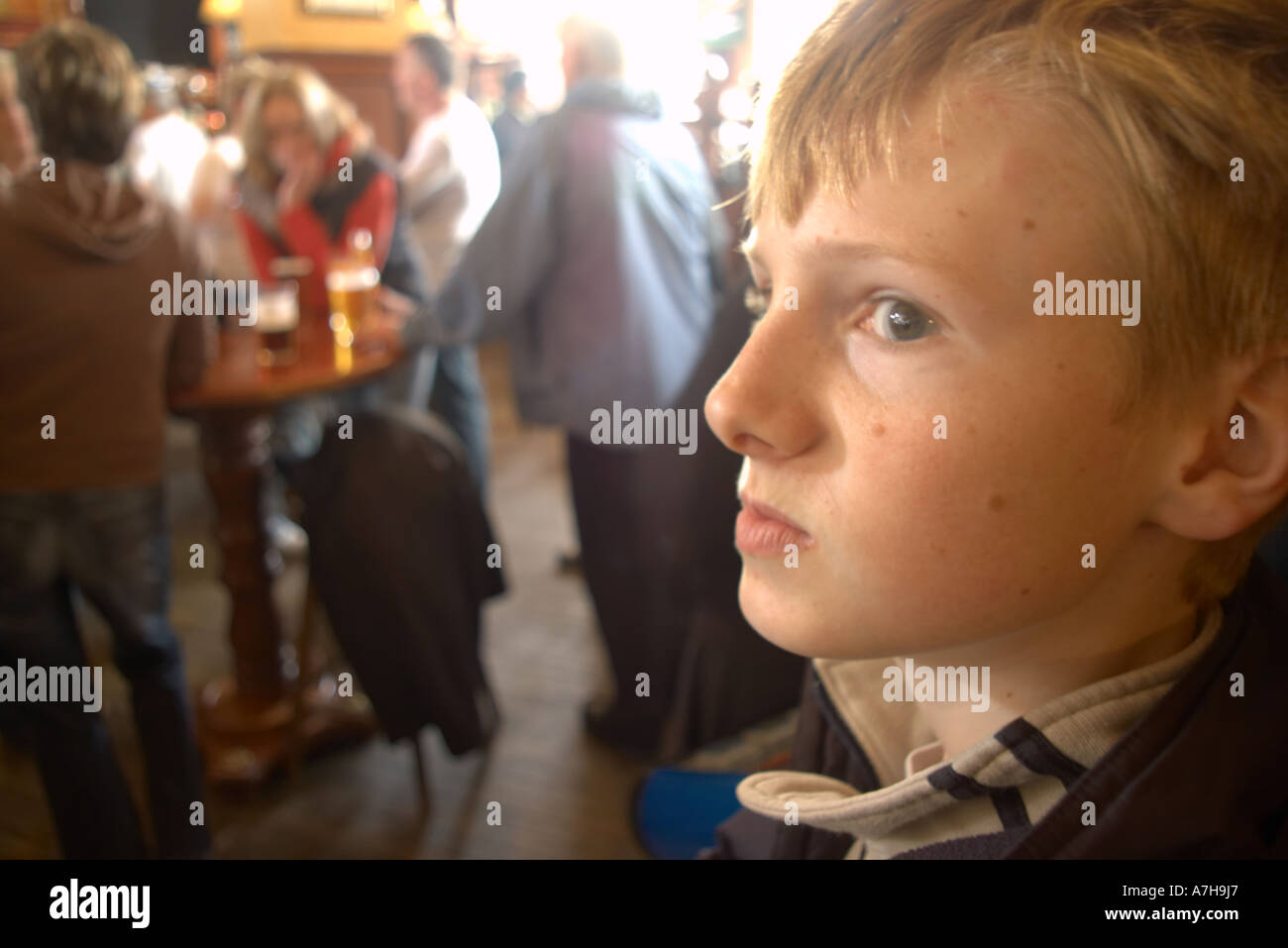 wary looking boy in pub with adults drinking beer in background - Stock Image