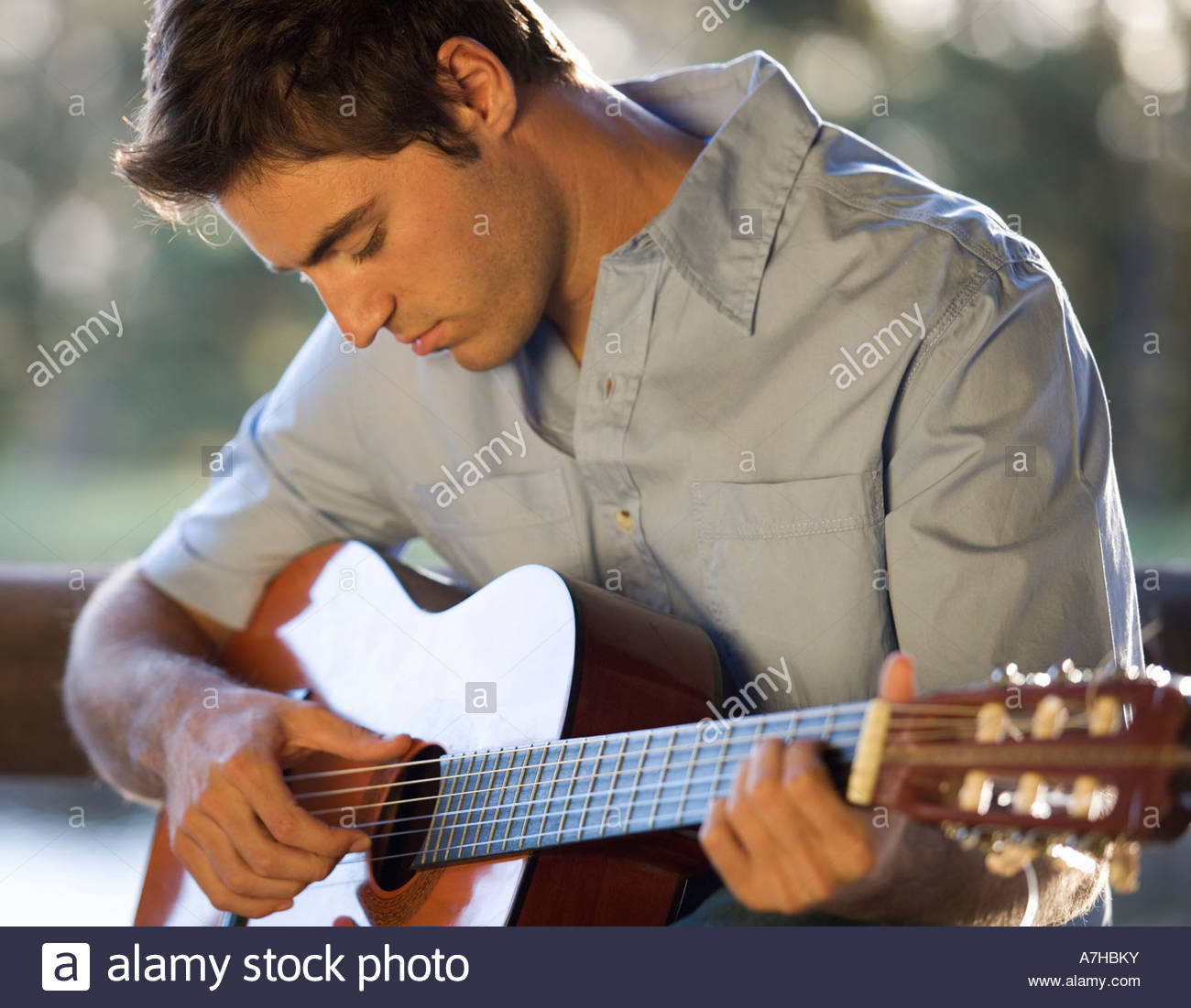 A young man playing a guitar - Stock Image