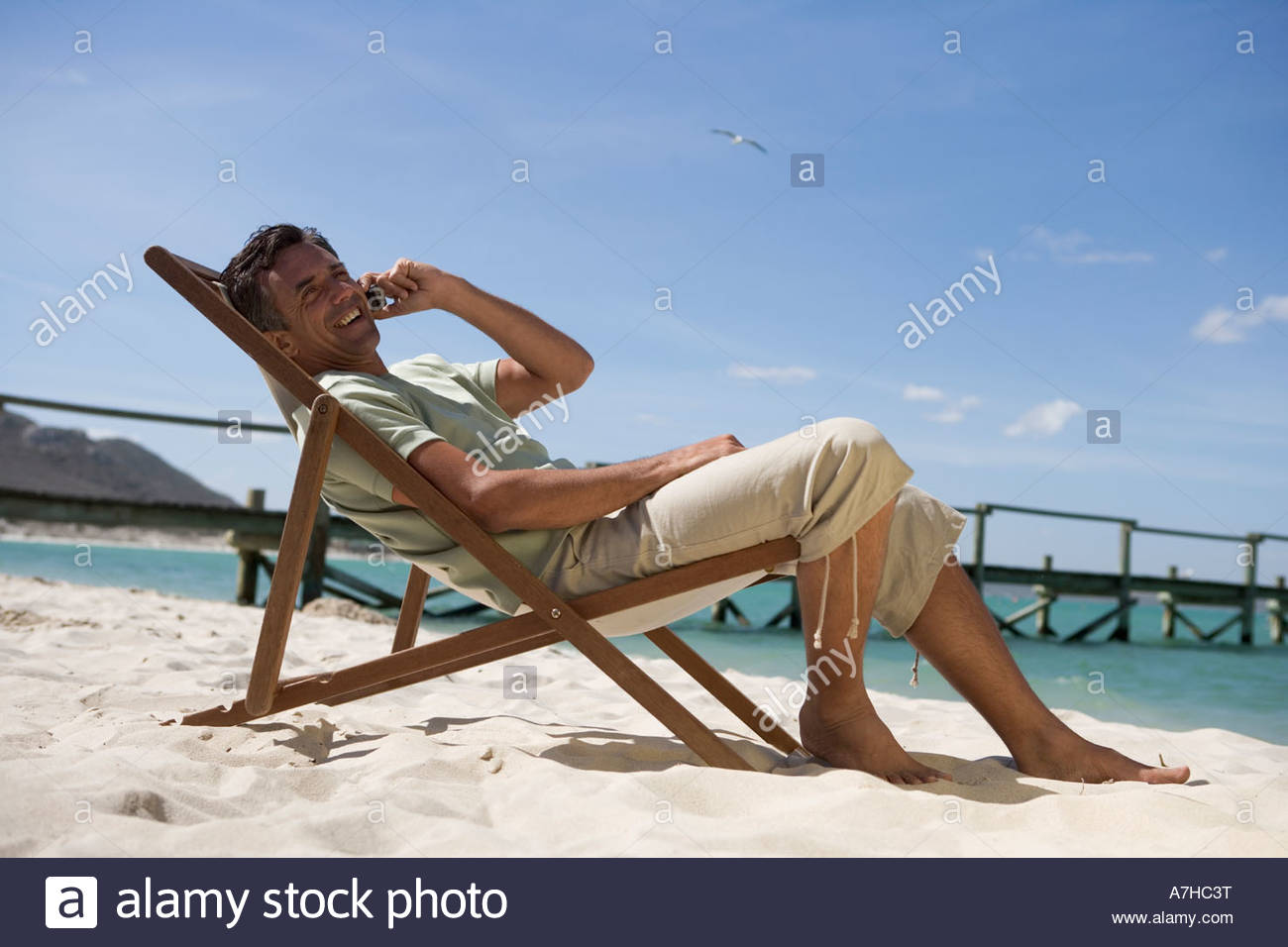 A mature man sitting in a deck chair on a cell phone - Stock Image