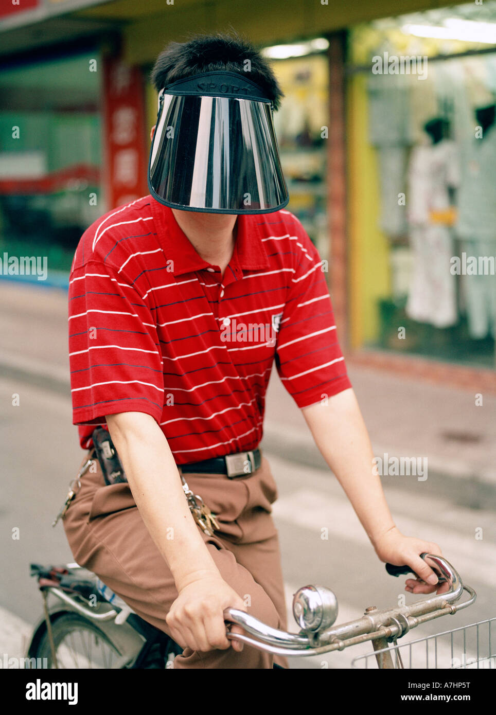 d825851d A Shanghainese Chinese man wears a protective shield to keep the sun off  his face as he rides his bicycle down the street