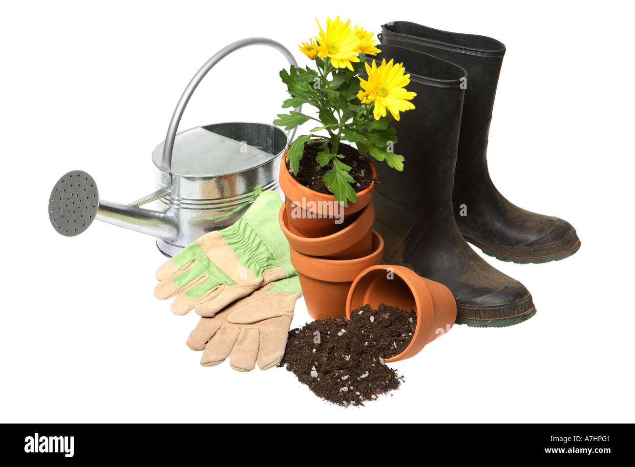 Garden things: watering can, gardening gloves, terra cotta pots, flowers, potting soil and rubber boots. - Stock Image