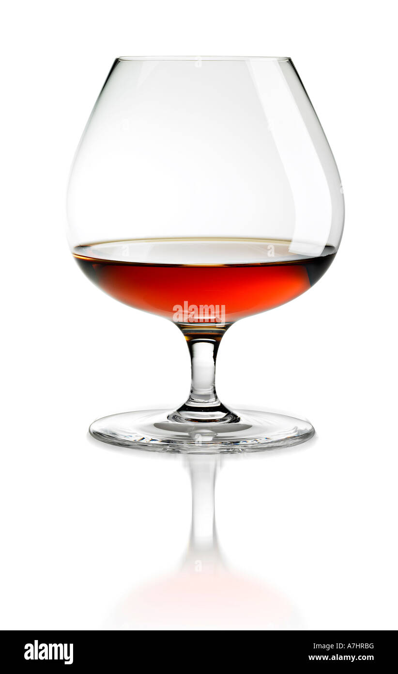 glass of cognac with reflection of glass on white background. Stock Photo