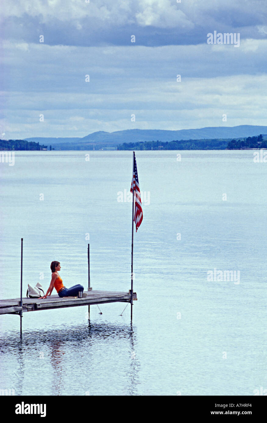 Woman Sitting on Dock with Flag on Lake Champaign Woman Wood Dock lake water American Flag Clouds Sky Blue Calm United States - Stock Image
