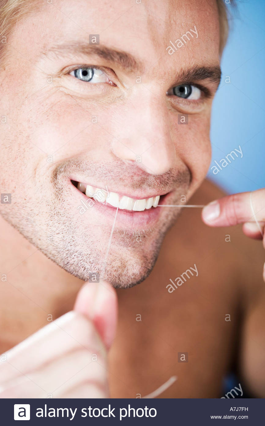 A young man flossing his teeth - Stock Image