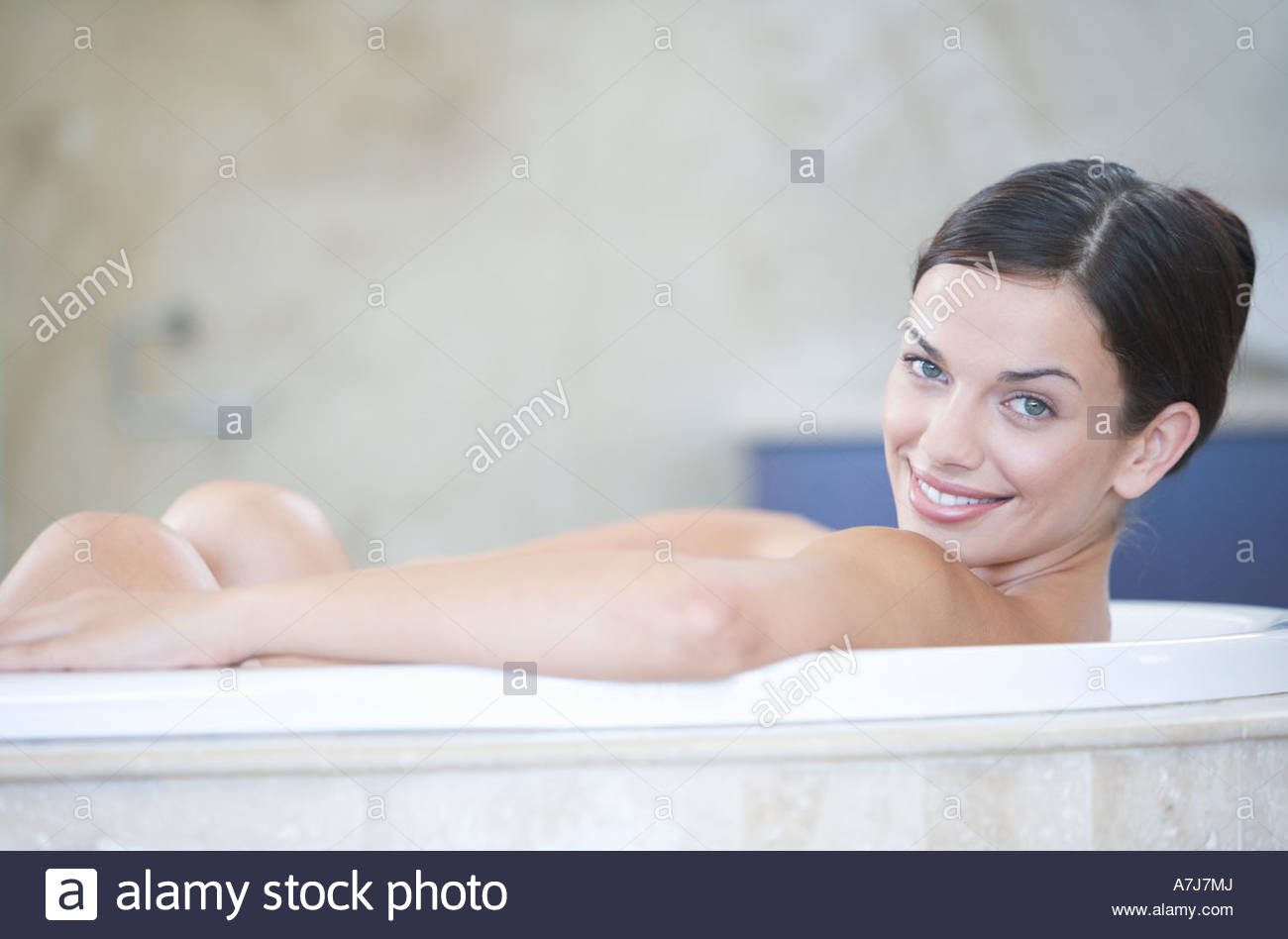 A young woman laying in a bath - Stock Image