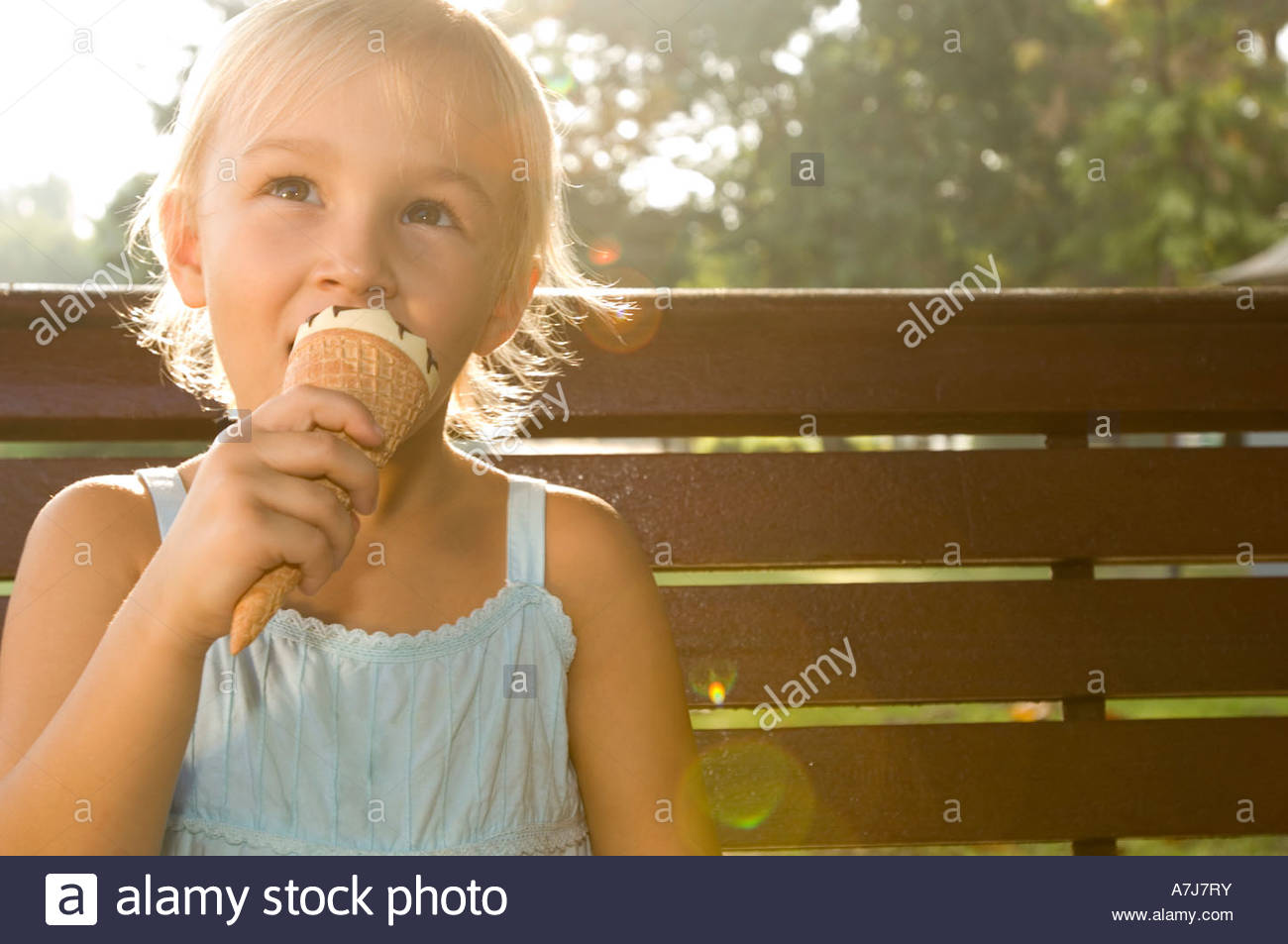 A young girl eating an ice cream - Stock Image