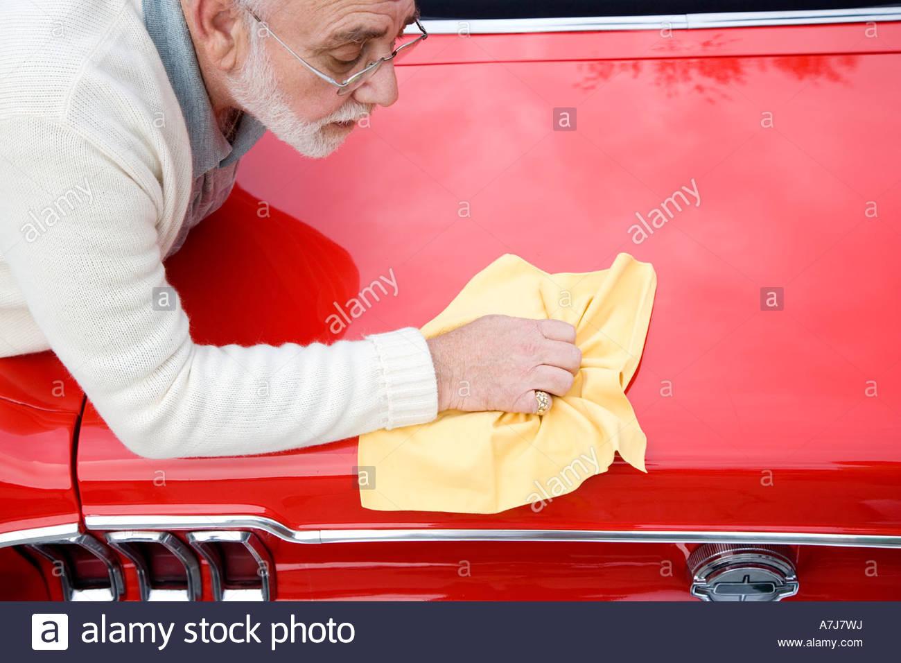 A senior man polishing a sports car - Stock Image