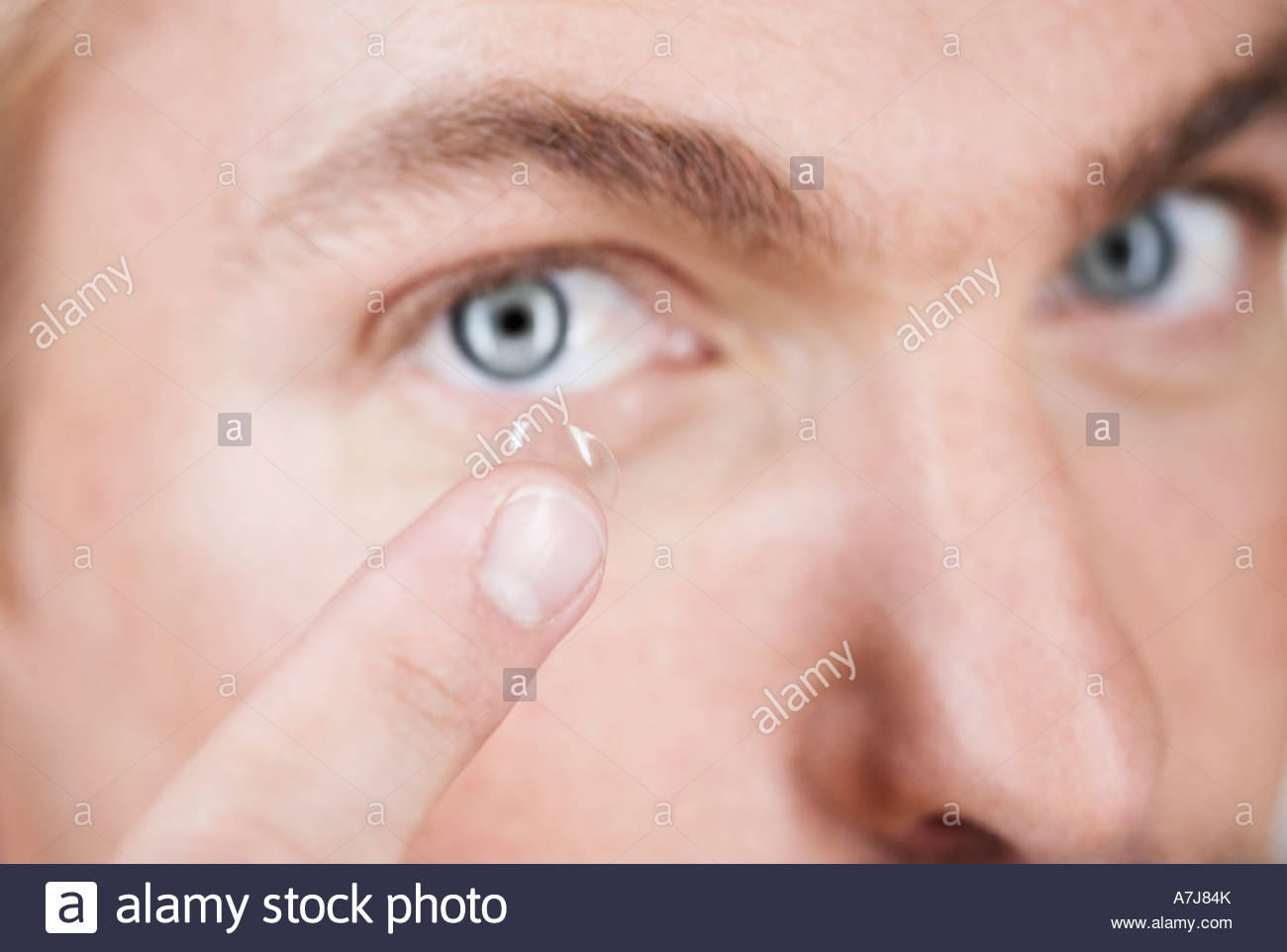 A young man inserting a contact lens - Stock Image