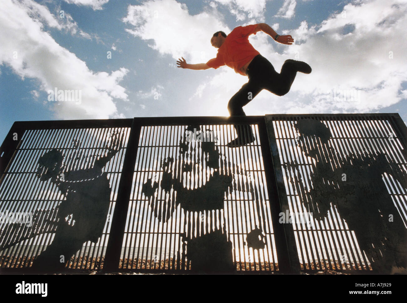 Sculptor Bruce Williams leaps over three of his laser cut fence panels for a public art project called Running Wall - Stock Image