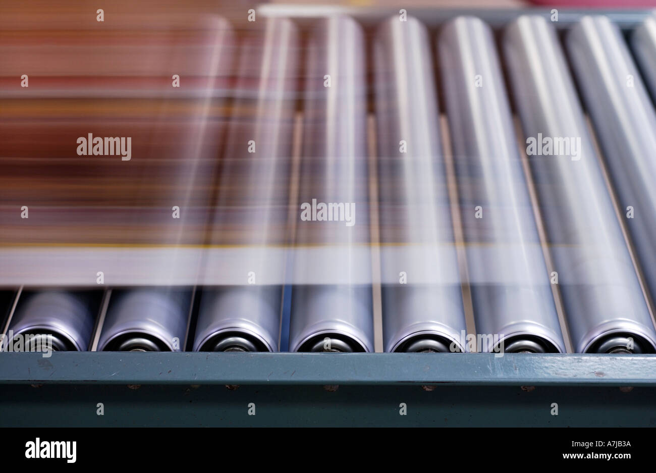 Product moving along steel rollers in factory - Stock Image