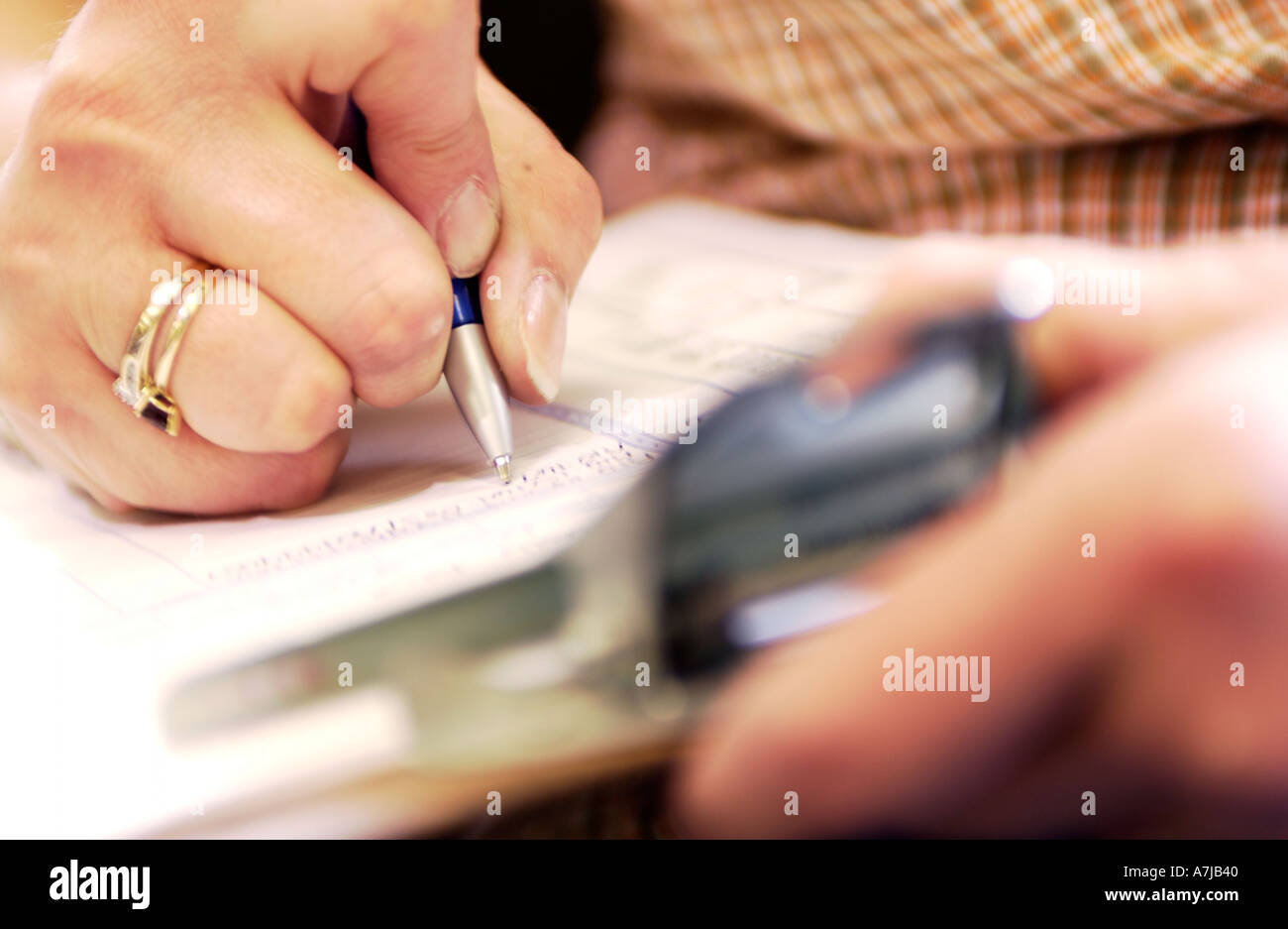 Detail of factory manager writing on clipboard - Stock Image