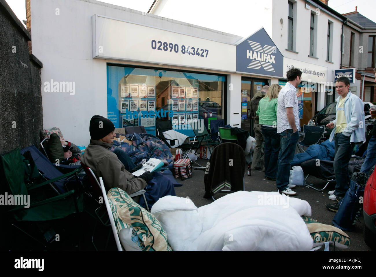 group of first time buyers camped outside an estate agency in northern ireland awaiting release of new development - Stock Image