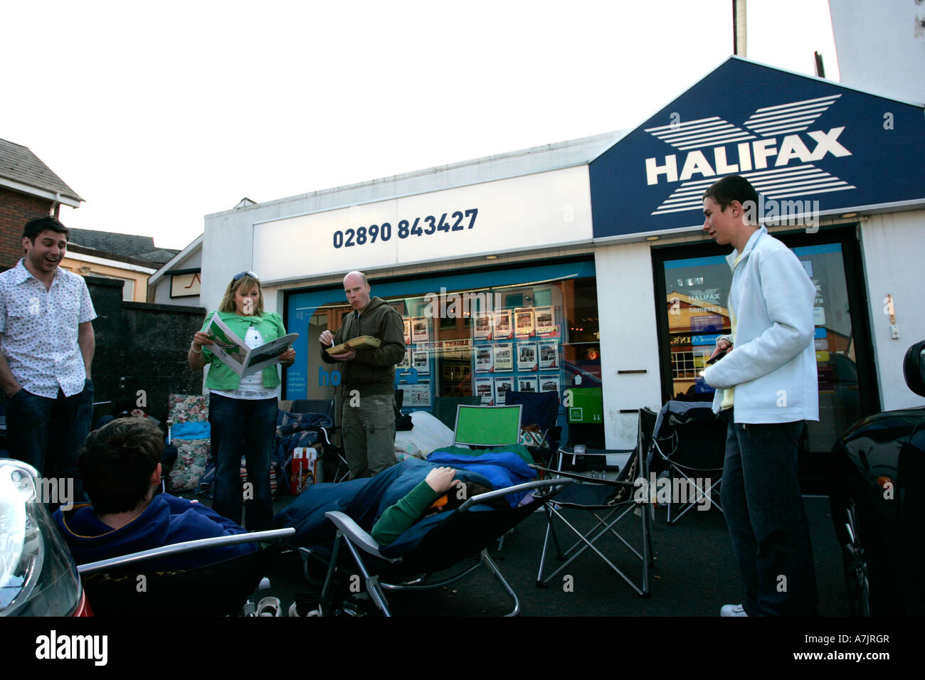 group of first time buyers standing and waiting camped outside an estate agency in northern ireland awaiting release - Stock Image