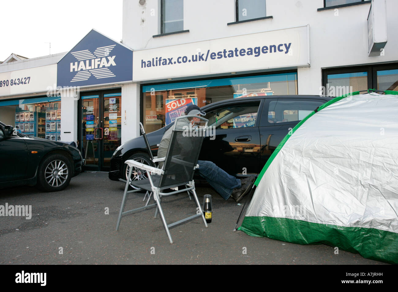 group of first time buyers camped outside an estate agency in northern ireland with cars and tent awaiting release - Stock Image