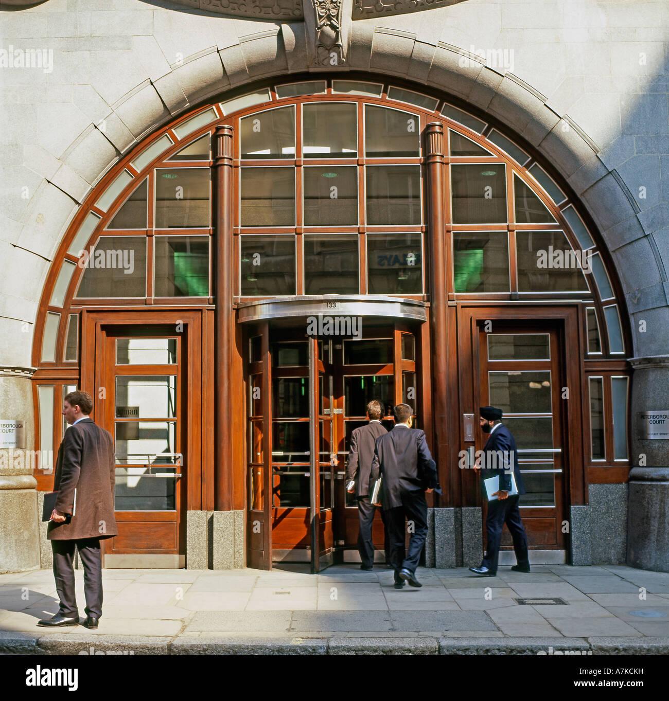 Businessmen outside the entrance of Goldman Sachs Office headquarters  in Fleet Street City of London England UK - Stock Image
