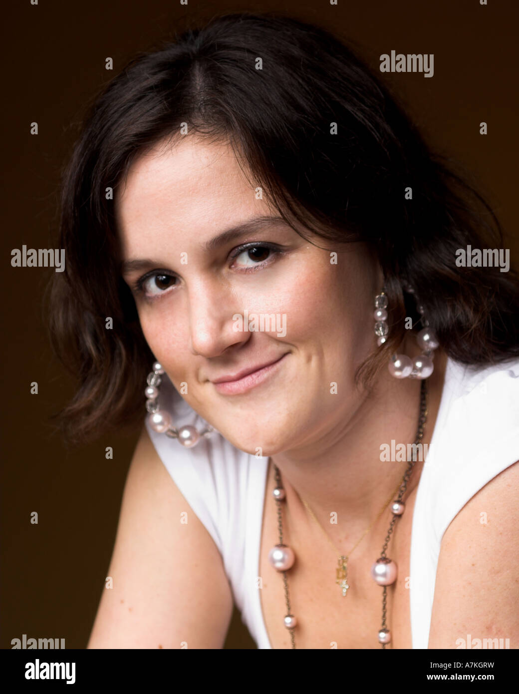 Studio indoor portrait of young woman on brown background Stock Photo