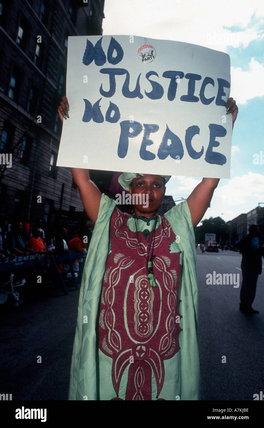 A protester marches in the African American Day Parade in Harlem with a No Justice No Peace sign  - Stock Image