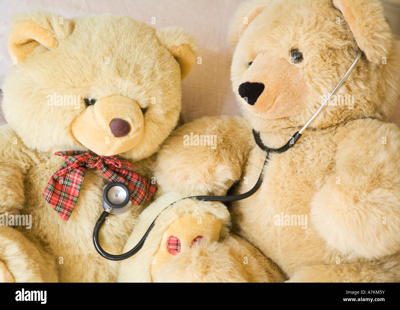Teddy bears with stethoscope posing as doctor and patient. Ideal to illustrate paediatrics. - Stock Image