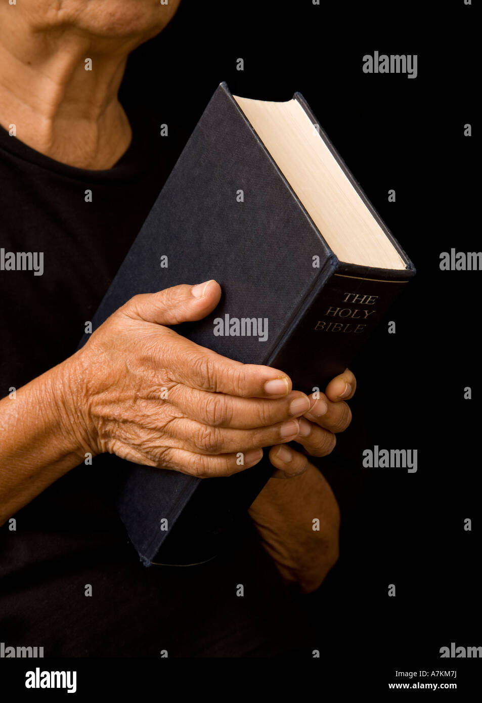 An old woman holds a bible in prayer Stock Photo: 11864021