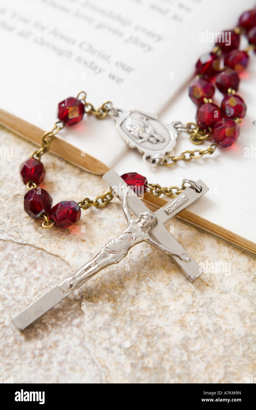 Rosary beads on a book of psalms and sandstone background Stock Photo
